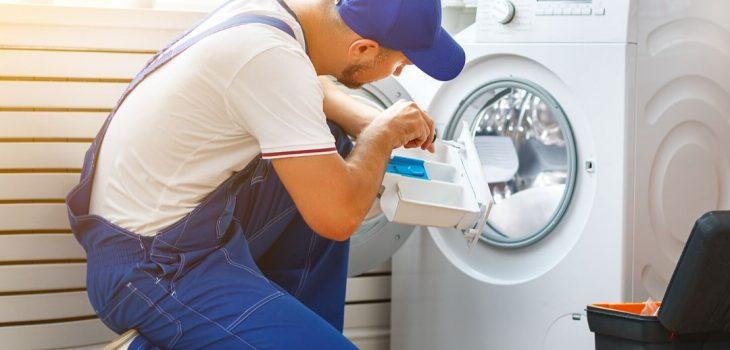 En installatör gör i ordning tvättmaskinen.