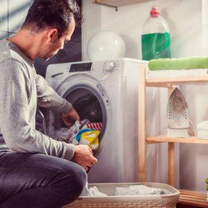 Man plockar upp tvätten från tvättmaskinen.