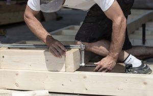 En snickare bygger ihop en altan i trä.