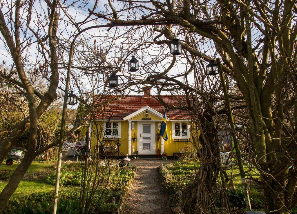 Gul liten trävilla med svensk flagga på sidan av ytterdörren